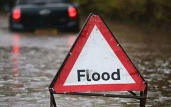 Warning sign on a flooded road.